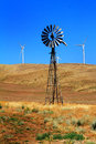 Old and new dependable energy an windmill still being used to generate pull water up in the pioneer cowboy era in western american Royalty Free Stock Images