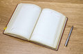 old open book with fountain pen on wooden table Royalty Free Stock Photo