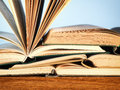 Old open novel books on a wooden table close up of pile of with copy space blue Stock Photos