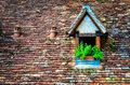 Old orange brick roof with window and flowers Royalty Free Stock Photos