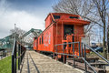 Old orange caboose train on a cloudy day and a bridge in the background Stock Image
