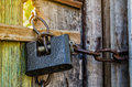 Old padlock with chain on wooden gate Royalty Free Stock Image