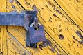 Old padlock on a wooden door yellow with rusty metal Royalty Free Stock Image