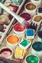 Old paintbox with watercolours. Vibrant colours used on the palette, brush with red paint Royalty Free Stock Photo