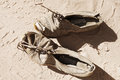 Old pair of shoes on sand