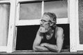 Old passive man lost in thought perched on window seal Royalty Free Stock Photography