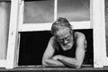 Old passive man lost in thought perched on window seal Stock Images