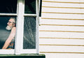 Old pensive man standing alone in window of house. Royalty Free Stock Photo