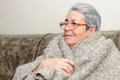 Old people person blanket cold senior female lady indoor home in glasses sitting shoulders Stock Image