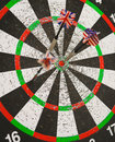 Old perforation dartboard with flags on darts focus center of target Royalty Free Stock Photography