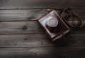 Old photo camera in leather case on wood table Royalty Free Stock Photography