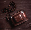 Old photo camera in leather case on wood table toned low contrast Stock Images