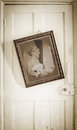 Old photograph of bride in antique frame hanging on worn door Stock Photos