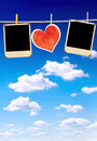 Old photos and paper heart on blue sky Stock Image
