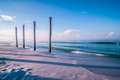 Old pier pile support columns standing along the beach Royalty Free Stock Photo