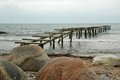 Old pier in the sea with boulders on foreground Royalty Free Stock Photos