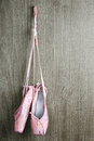 Old pink ballet shoes used hanging on wooden background Stock Images