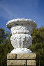 Old plaster garden vase on a modern brick pedestal Royalty Free Stock Photo