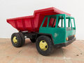 Old plastic dump toy a red and green on a ground Royalty Free Stock Photography