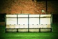 Old plastic seats on outdoor stadium players bench, chairs with worn paint below yellow roof. Royalty Free Stock Photo