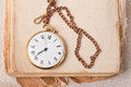 Old pocket watch and a book on the background of old cloth Royalty Free Stock Photography