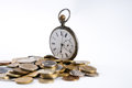 Old pocket watch with open cover on scattered coins  on white with copy space Royalty Free Stock Photo