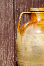 Old pot brown terracotta jar. Background old grunge wood. Royalty Free Stock Photo
