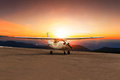 Old propeller plane taxi on airport runway against beautiful sun Royalty Free Stock Photo