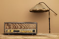 Old radio on wooden table with floor lamp brown wall Royalty Free Stock Photos