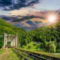 Old railroad passes in mountain village at sunset through the metal bridge the Royalty Free Stock Photography