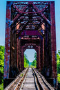 Old railroad trestle with an old iconic iron truss bridge vanishing point view of over the brazos river texas Royalty Free Stock Images