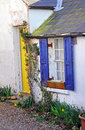 Old ramshackled country cottage photo of a quaint kent with bright yellow door and bright blue window shutters Stock Photo