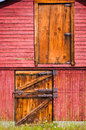 Old red barn doors the side of an with closed door and hay loft and weathered tin roof Royalty Free Stock Images