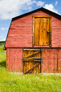 Old red barn the side of an with closed door and hay loft and weathered tin roof Royalty Free Stock Photography