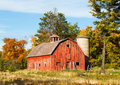 Old red barn and silo an with is surrounded by trees with colorful fall foliage shot in rural wisconsin Royalty Free Stock Images