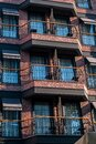 Old red brick wall building with balconies and sunshades on the windows Royalty Free Stock Photo