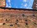 Old red brick wall and tiled roof of a medieval castle against the blue sky with white clouds. The background Royalty Free Stock Photo