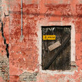 Old red decadent wall with a closed window warning of danger Royalty Free Stock Images