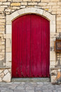 Old red door against an old stone wall Royalty Free Stock Photo