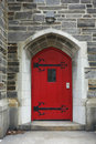 Old red door an wooden on a stone building Royalty Free Stock Photo