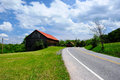 Old red roof barn near highway Royalty Free Stock Photo