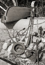 Old red rowboat lays on the coast near rusted anchors and chains monochrome toned photo retro style Stock Images