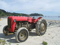 Old red tractor on a beach Royalty Free Stock Photo