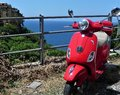 An old red Vespa scooter with sea in the background, Cinque Terre, Italy