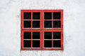 Old red weathered window with squares on white wall with worn texture. Royalty Free Stock Photo