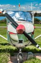 Old red and white single engine propeller airplane, front view, parked on grass field. Royalty Free Stock Photo