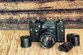 Old retro photo camera and film negative strip on wooden table a Royalty Free Stock Photo