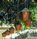 Old retro vintage lanterns hanging on background of green leaves Royalty Free Stock Photo