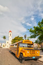 Old retro yellow school bus parked at jose marti park cienfuegos cuba may with cathedral of the immaculate conception catedral de Royalty Free Stock Image