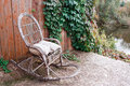 Old rocking chair on the front porch of an  house. wooden wall with vine grapes Royalty Free Stock Photo